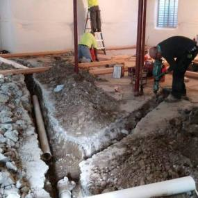 Construction company in Denver fixing pipes under concrete floors